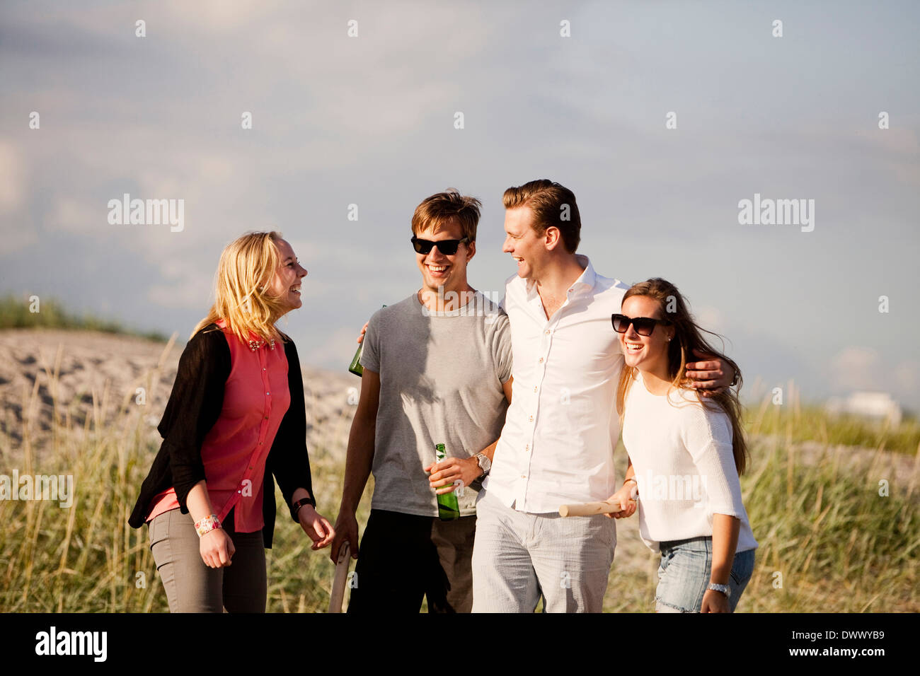 Happy male and female friends standing at beach - Stock Image