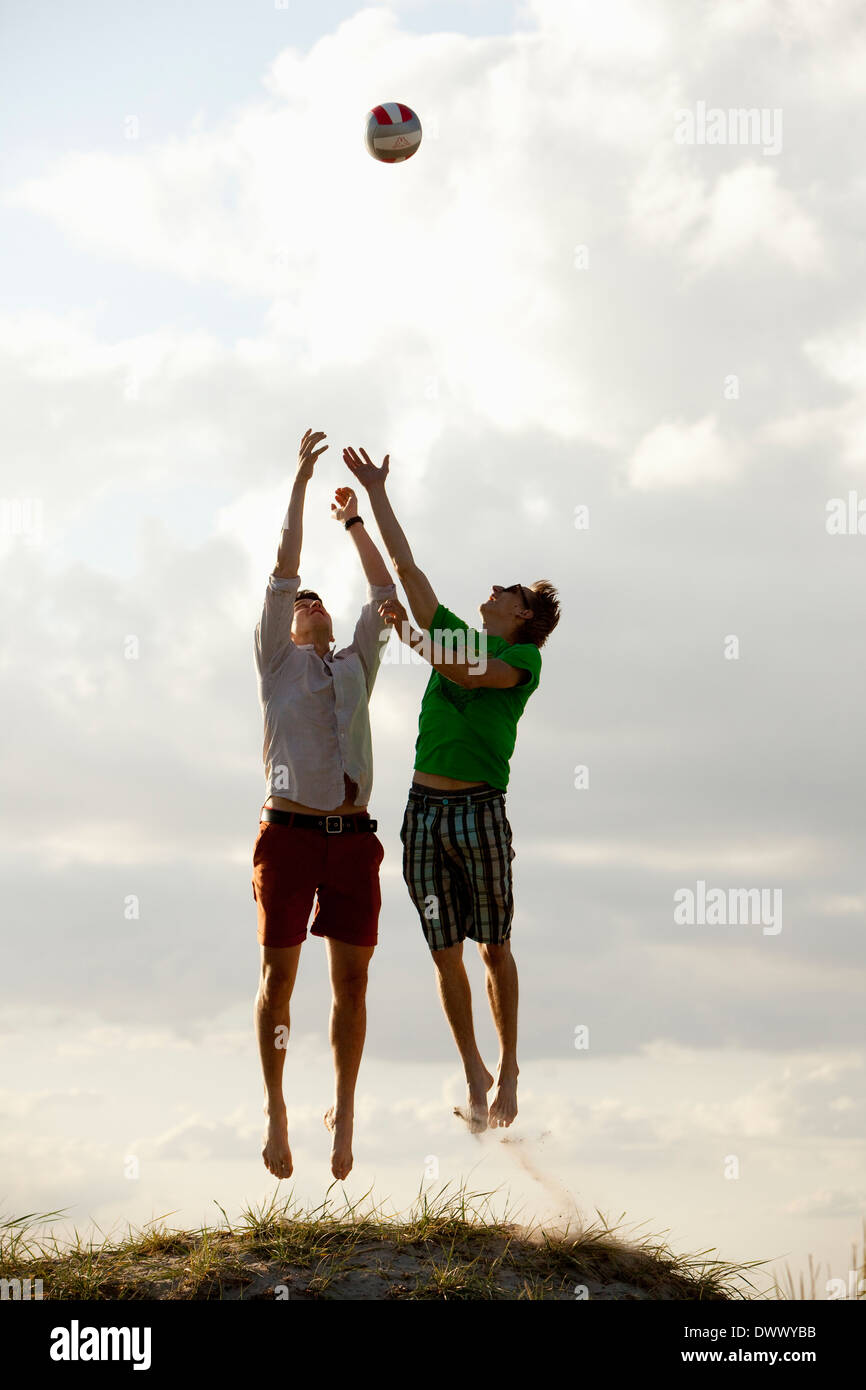 Two male friends in mid air trying to catch ball against sky - Stock Image