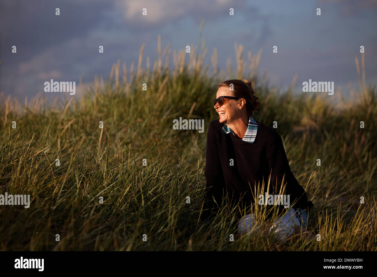 Happy woman sitting on grass - Stock Image