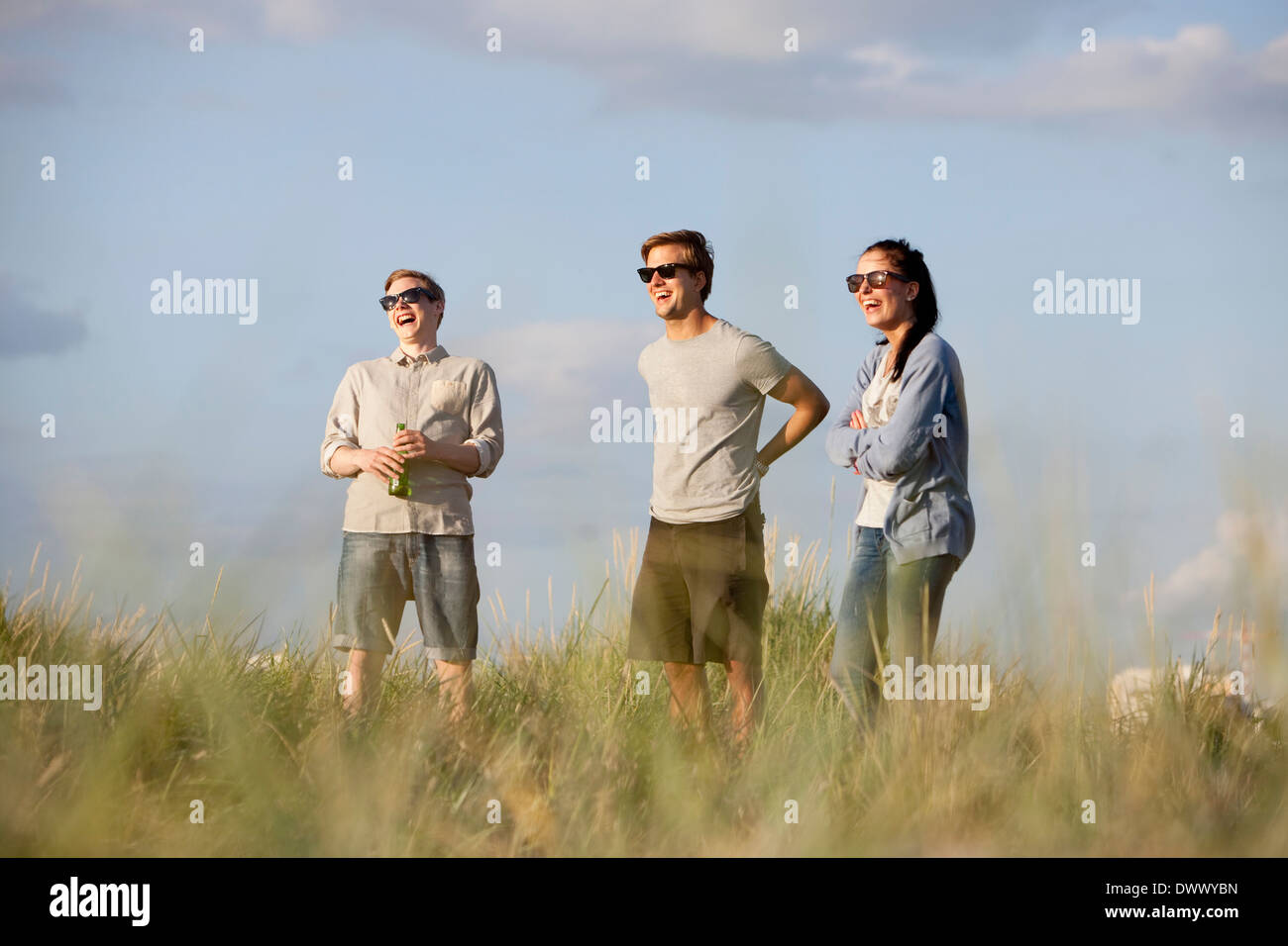 Young friends laughing against sky - Stock Image