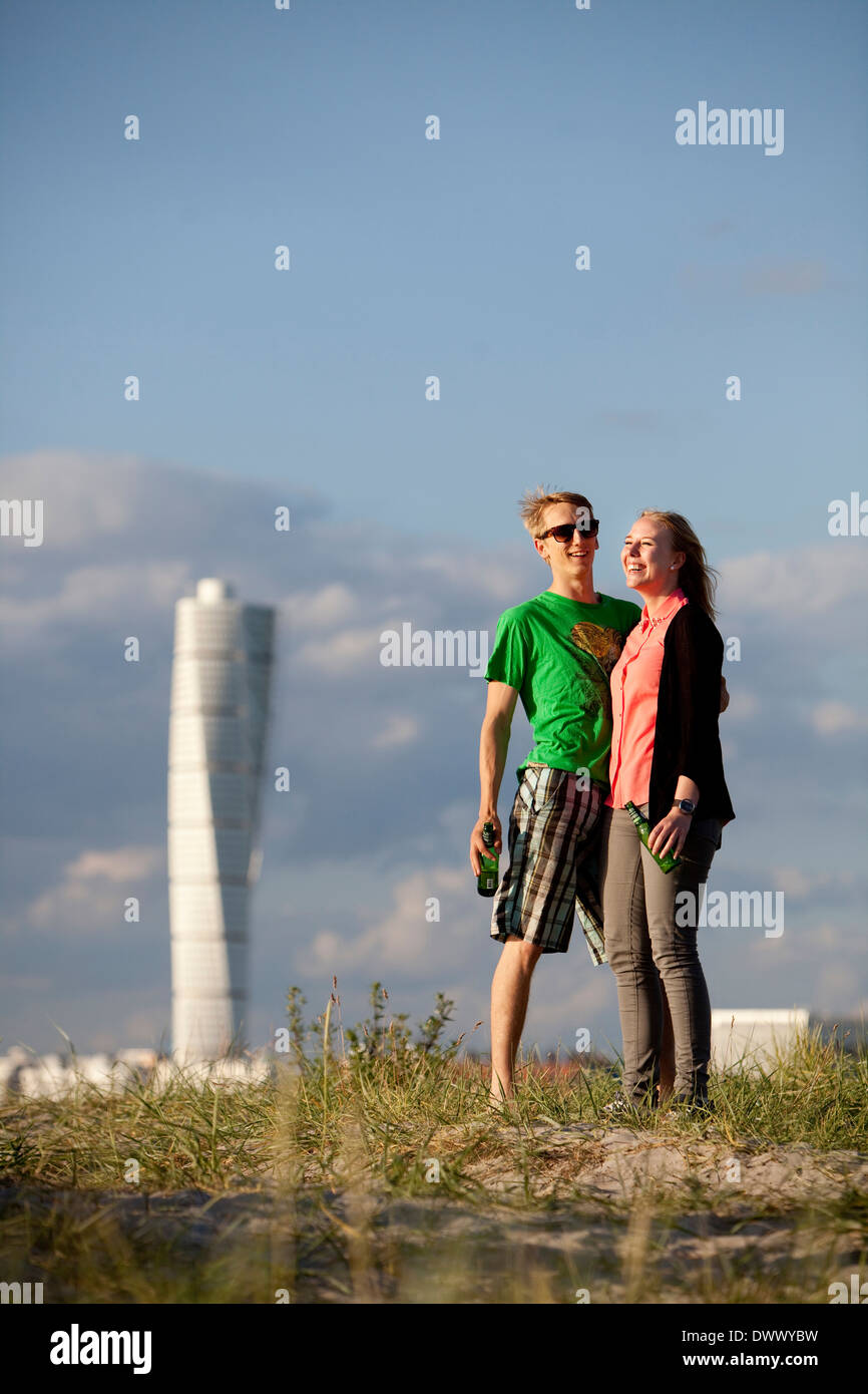 Young couple standing at beach - Stock Image