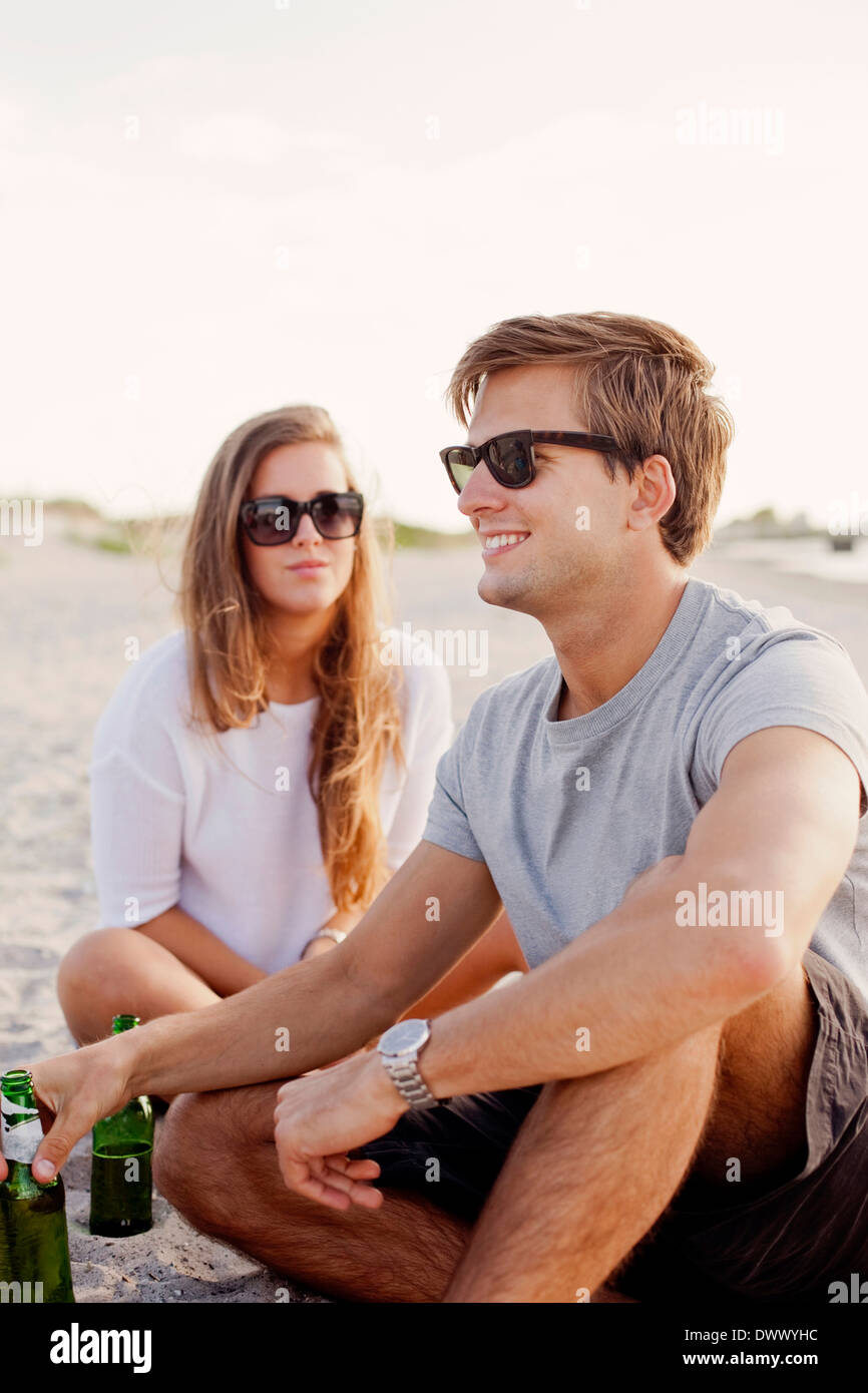 Smiling man holding beer bottle while woman looking at him on beach - Stock Image