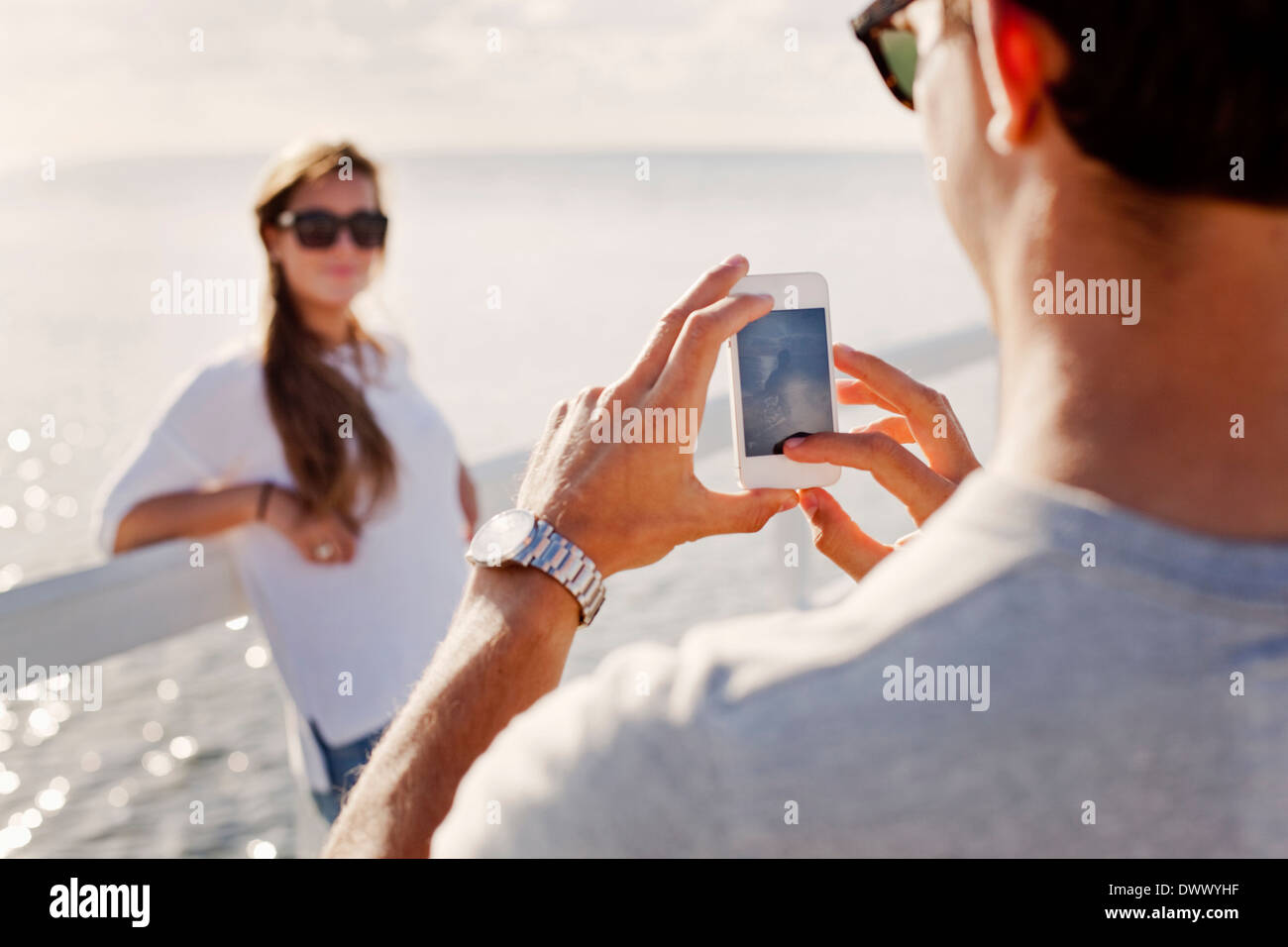 Man photographing woman through smart phone on pier - Stock Image