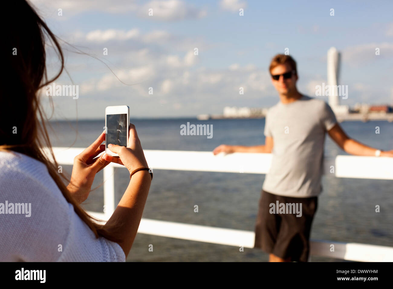 Woman photographing man through smart phone on pier - Stock Image