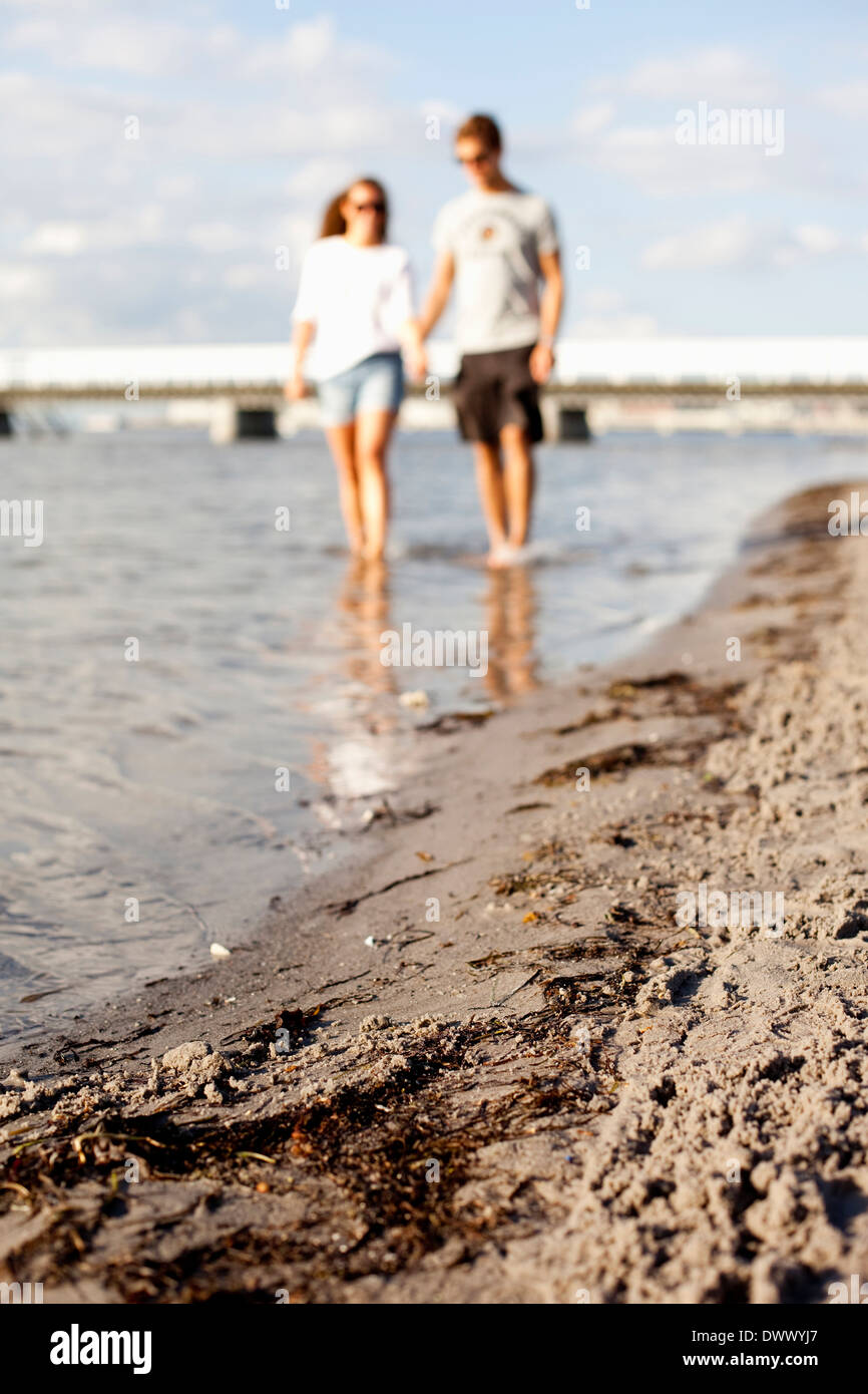 Couple walking in water at beach - Stock Image