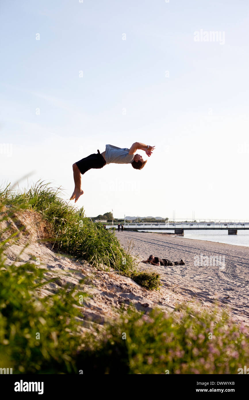 Full length of young man doing backflip on beach - Stock Image