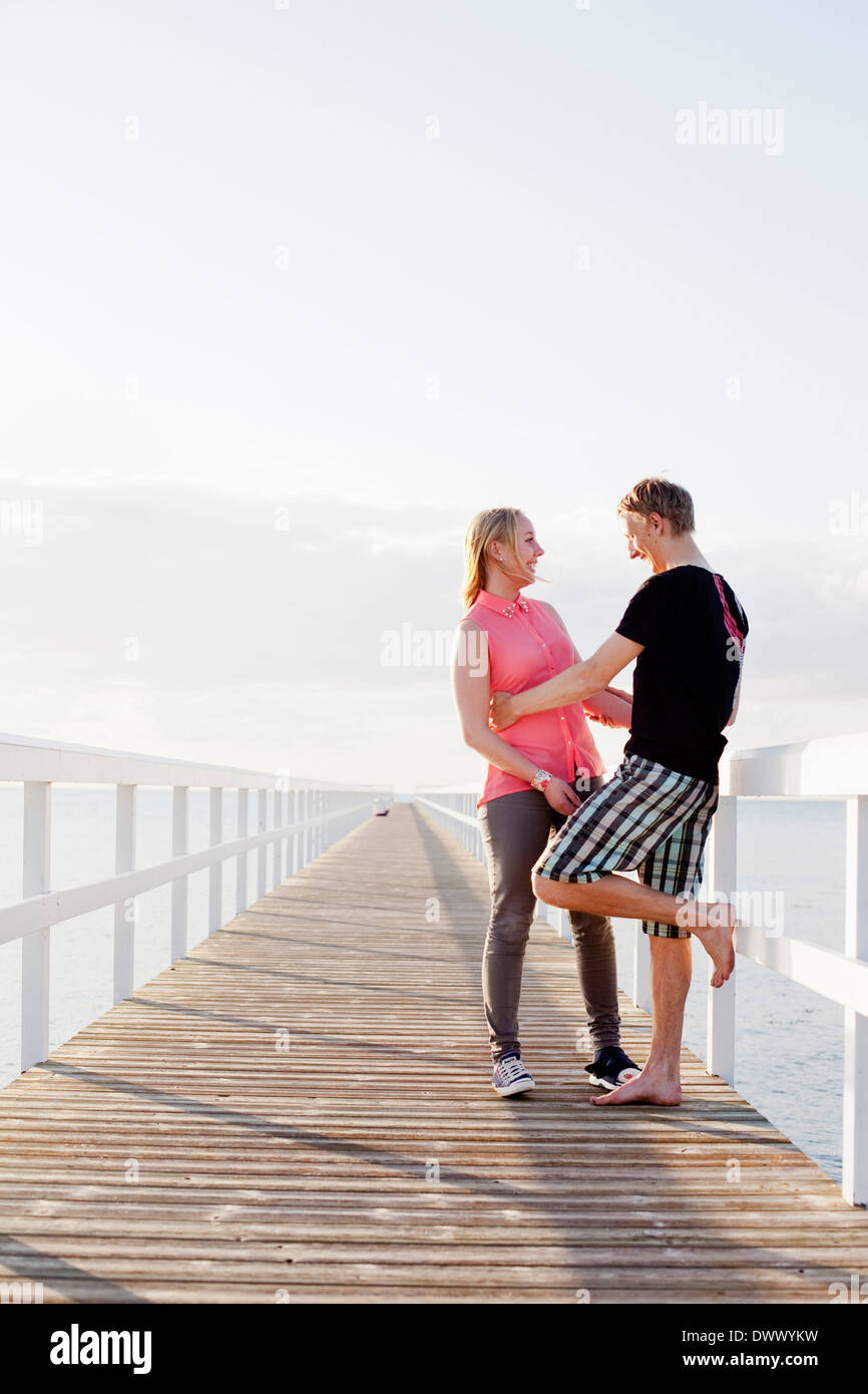 Happy young couple standing on pier - Stock Image