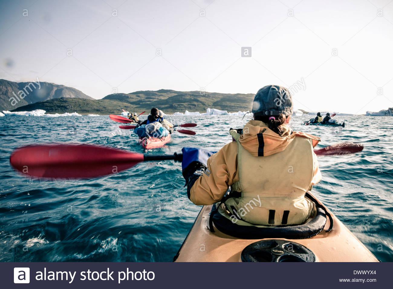 Rear view of mature woman kayaking on sea - Stock Image