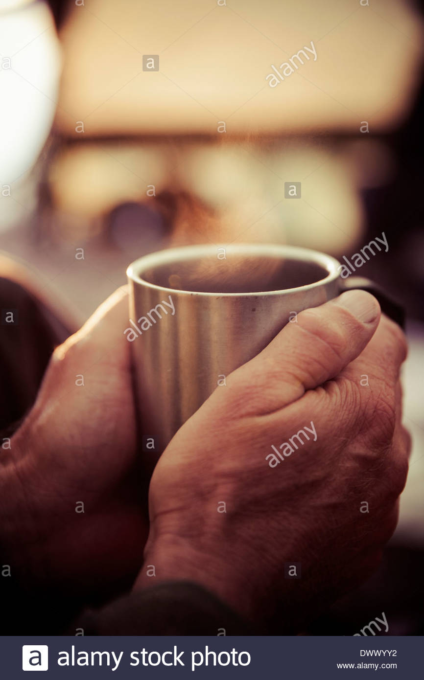 Man's hands holding coffee cup in tent - Stock Image