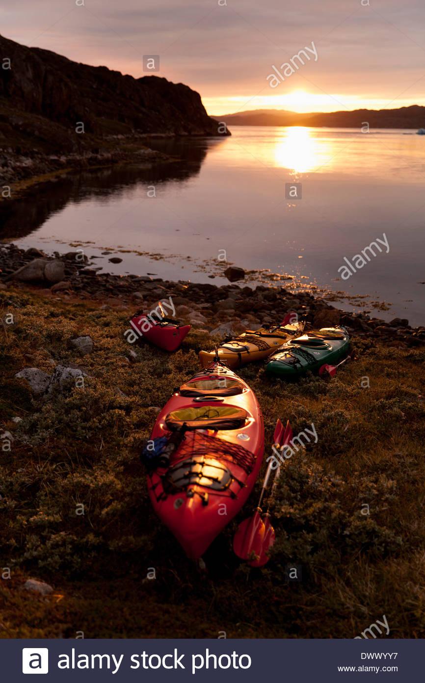 Kayaks moored on lakeshore at dusk - Stock Image