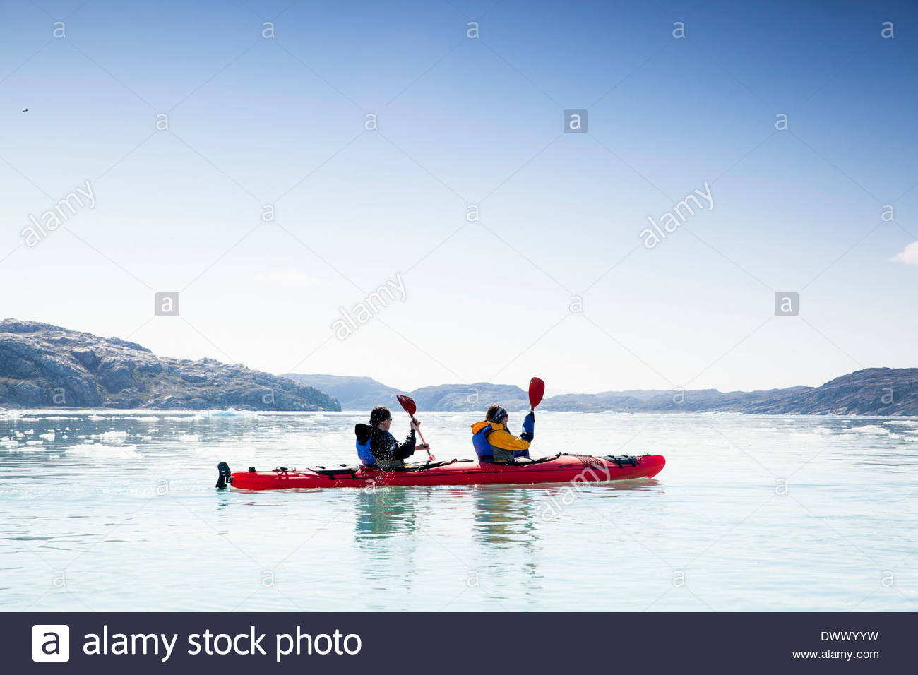 People kayaking on sea against clear sky - Stock Image
