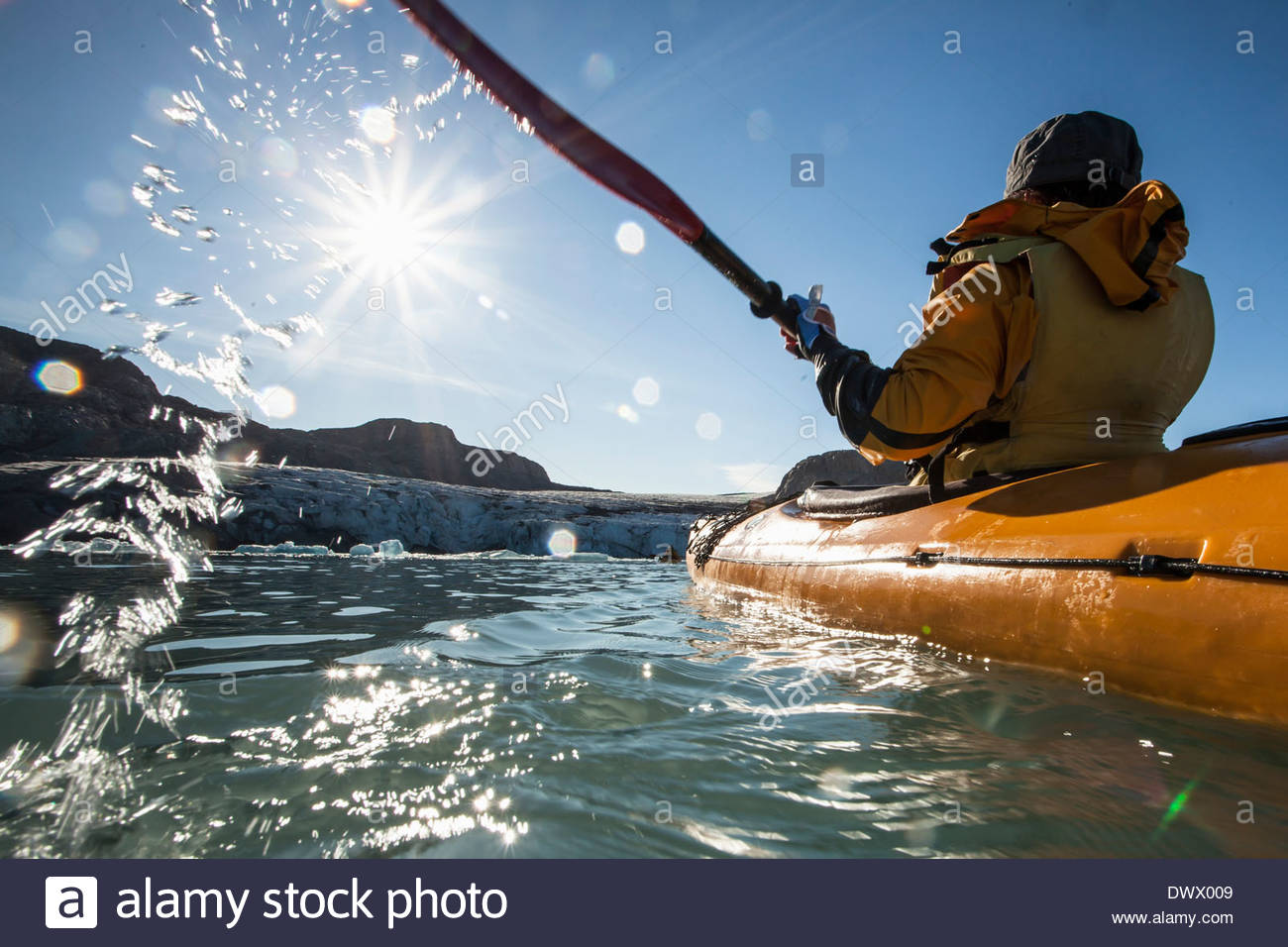 Rear view of mature woman kayaking on sea - Stock Image