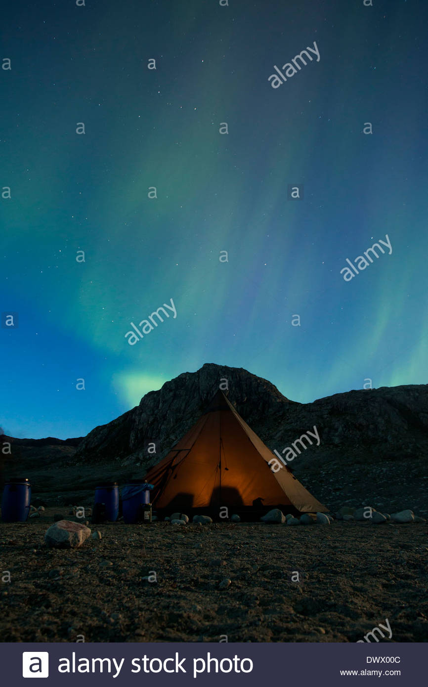 Northern lights or Aurora Borealis over tent at night - Stock Image