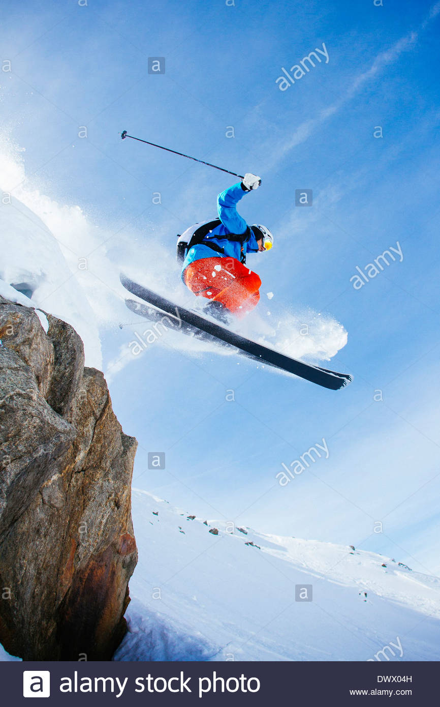 Low angle view of mid adult man skiing against sky Stock Photo