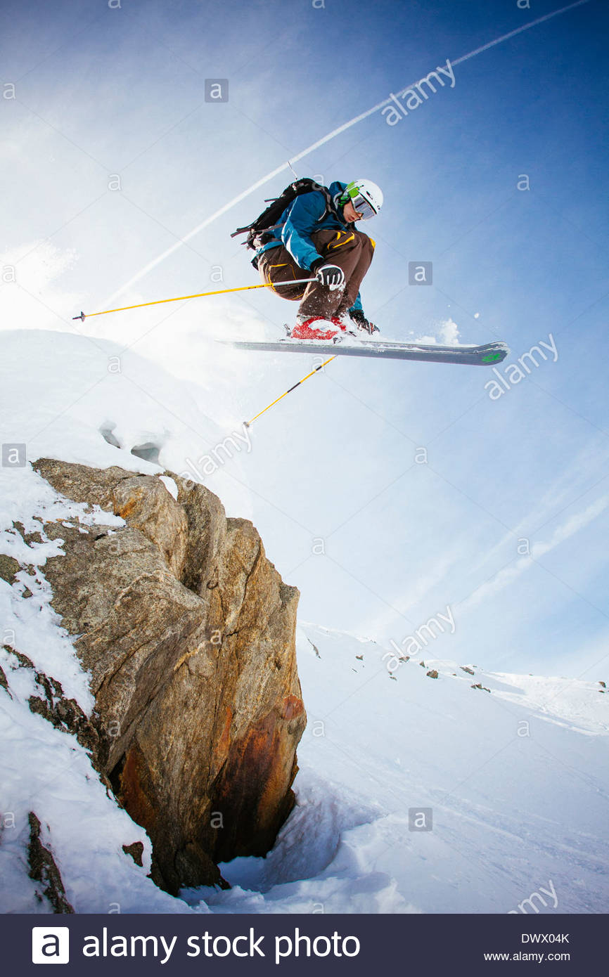 Full length of free ride skier in mid air against sky - Stock Image