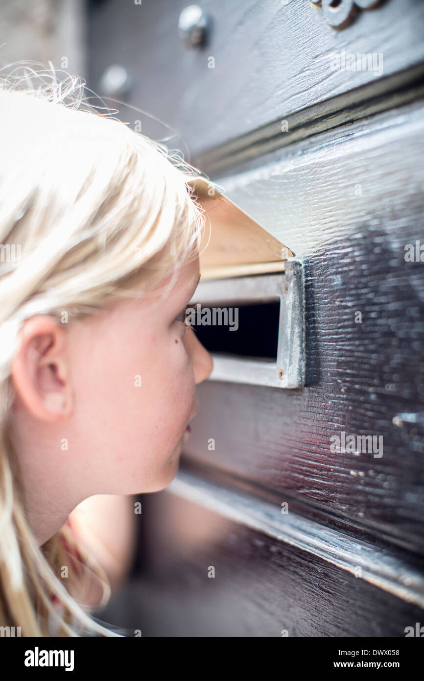 Side view of girl looking through mail slot in door - Stock Image