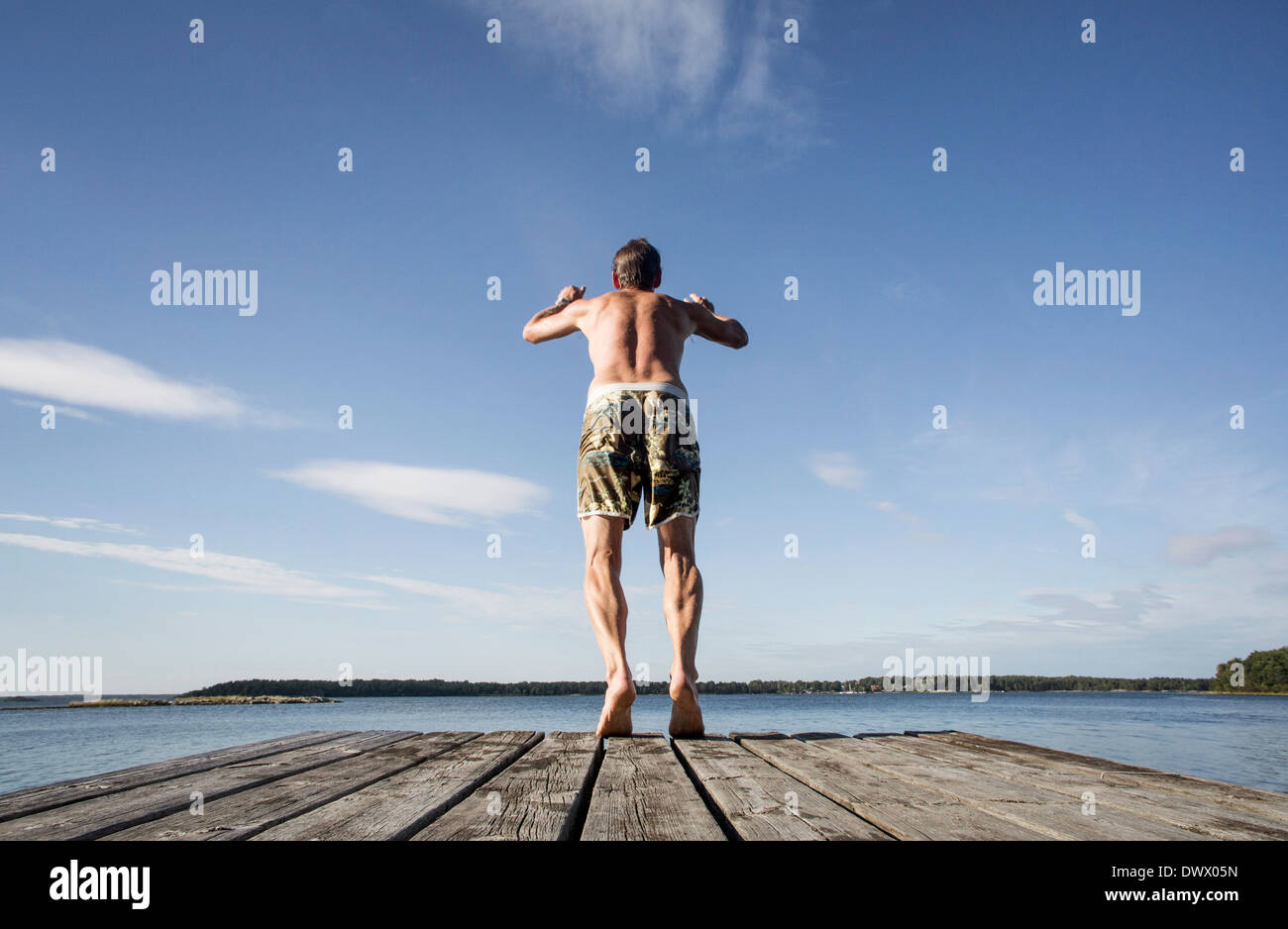 Rear view of mature man diving into sea - Stock Image