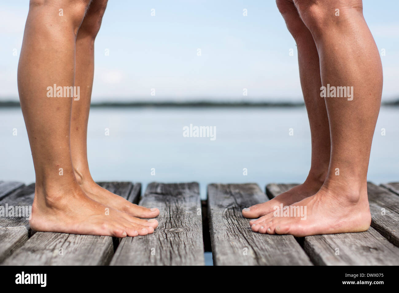Low section side view of women standing on pier - Stock Image