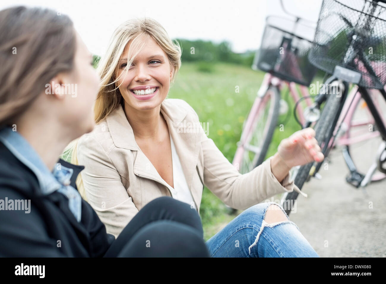 Happy young woman conversing with female friend on country road - Stock Image