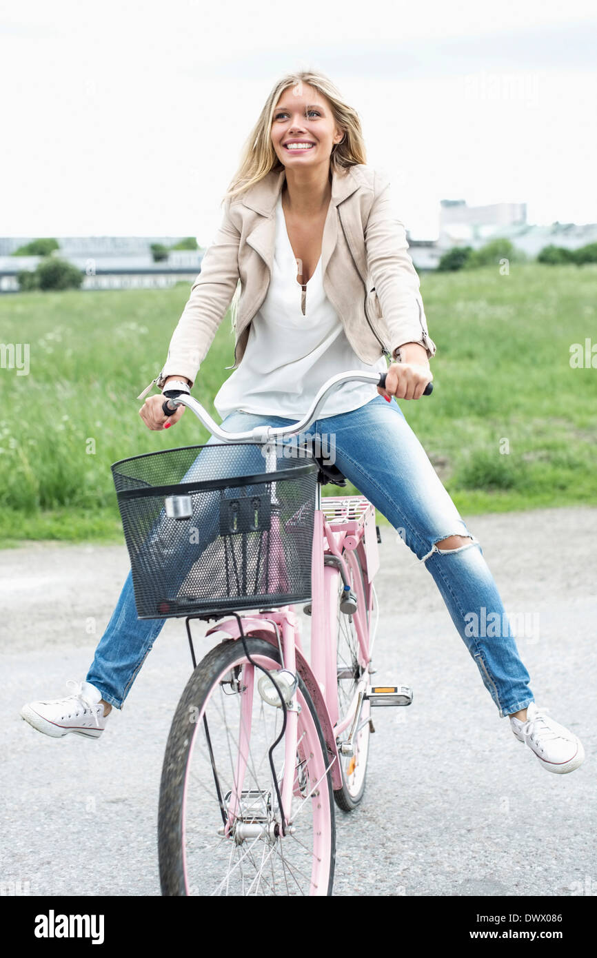 Thoughtful young woman sitting with legs apart on bicycle at countryside - Stock Image