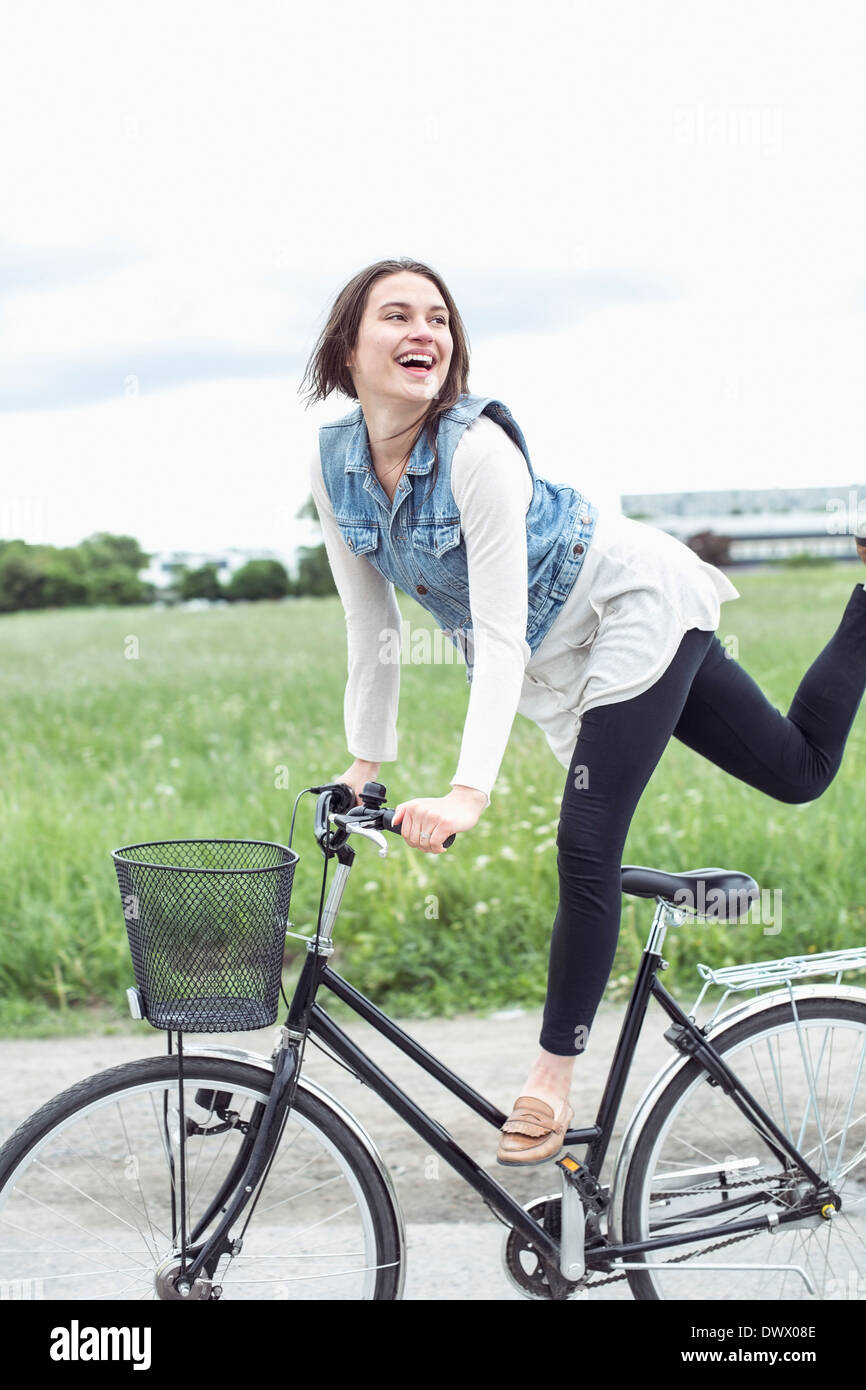 Happy young woman performing trick on bicycle at countryside - Stock Image