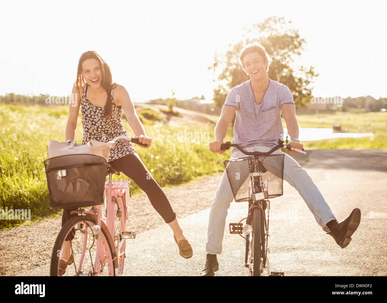 Portrait of happy young couple with legs apart cycling on country road - Stock Image