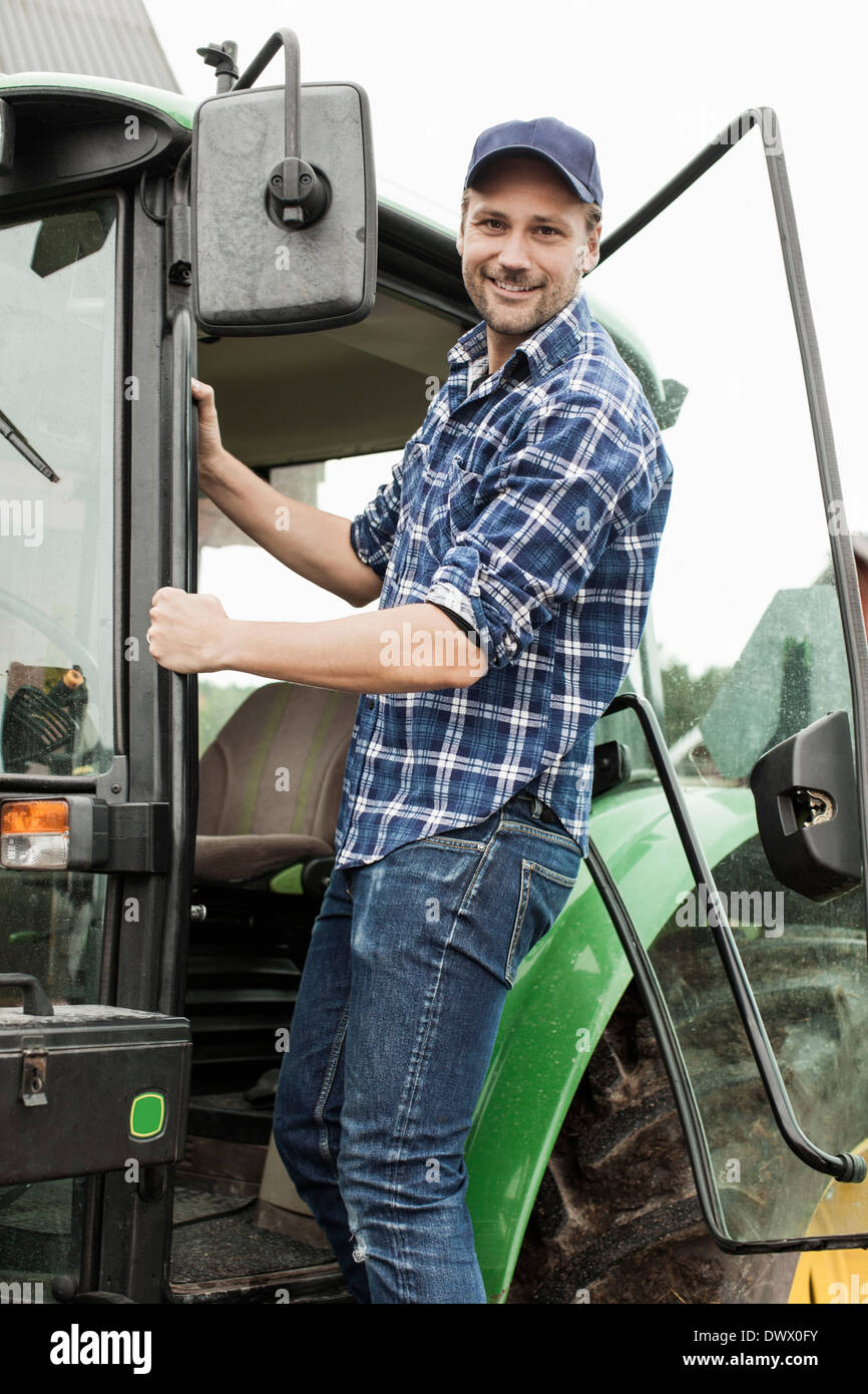 Portrait of smiling farmer entering tractor - Stock Image