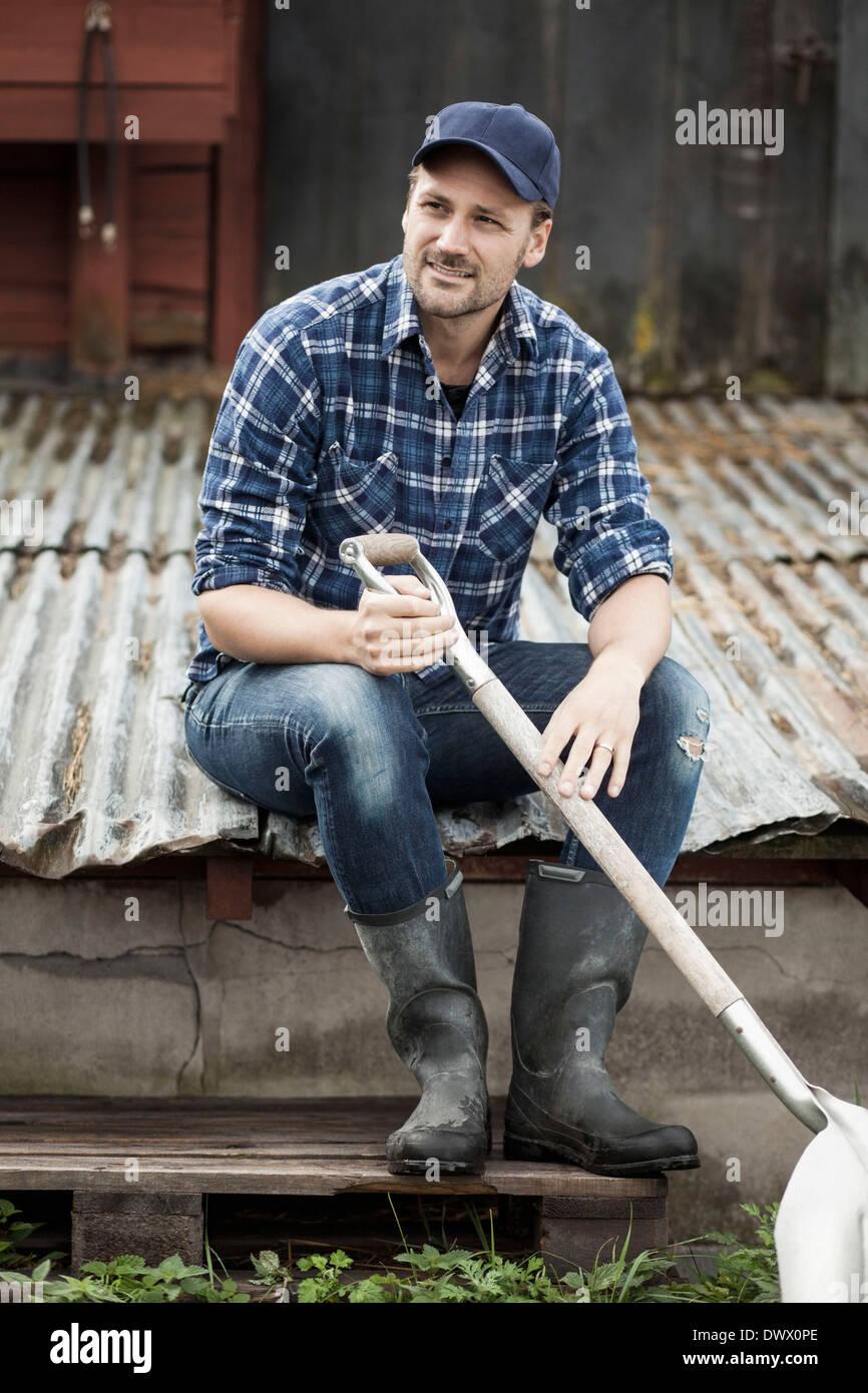 Full length of farmer with shovel sitting on corrugated iron at farm - Stock Image