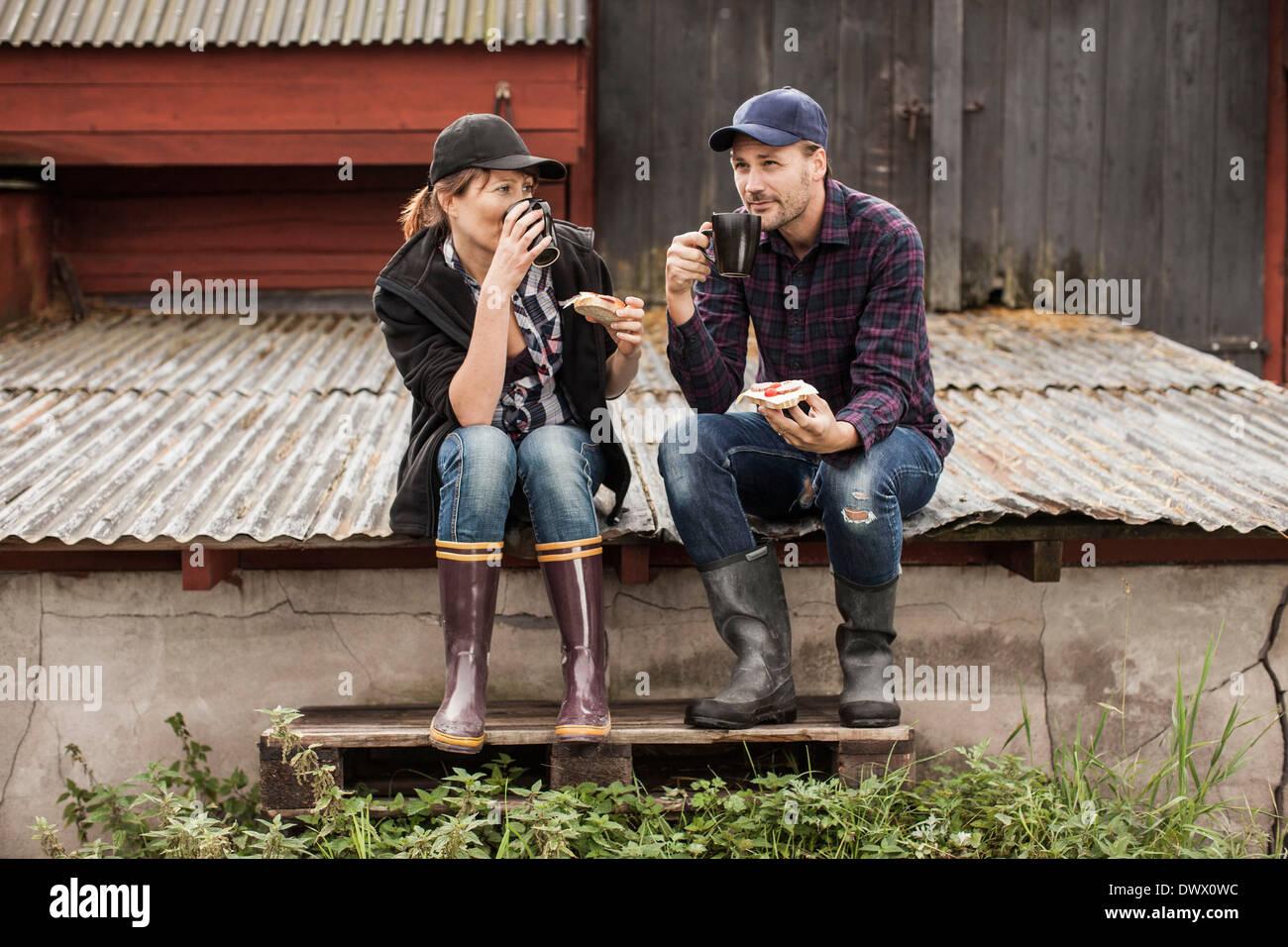 Full length of couple having breakfast on corrugated iron at farm - Stock Image