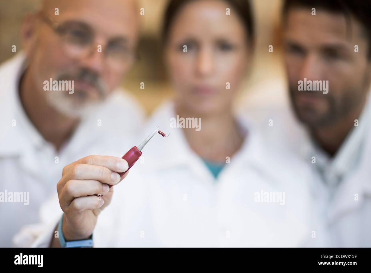 Engineers looking at resistor in manufacturing industry - Stock Image