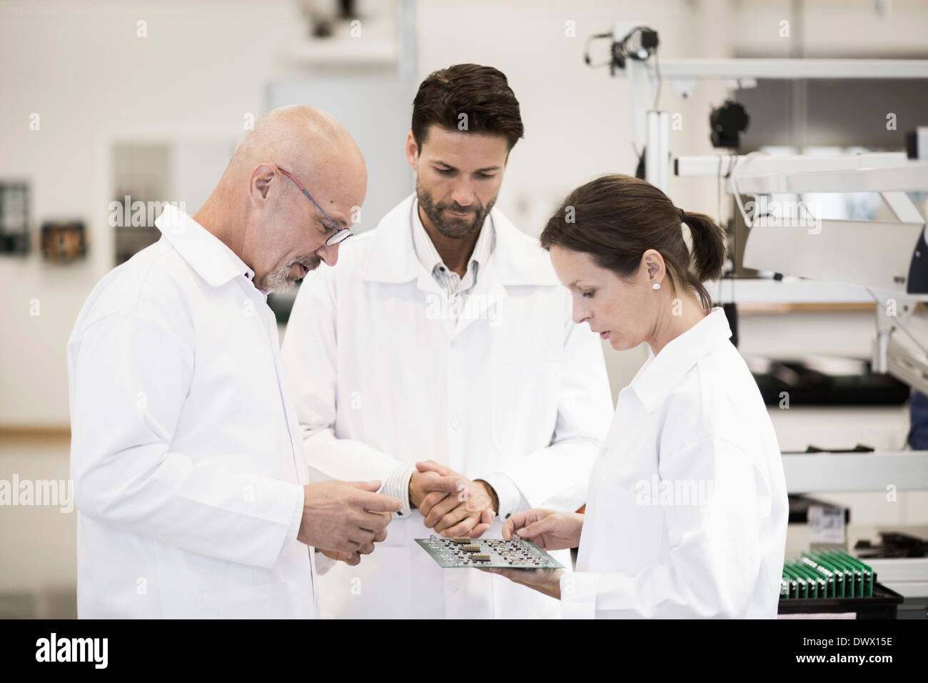 Team of technicians examining circuit board in factory - Stock Image