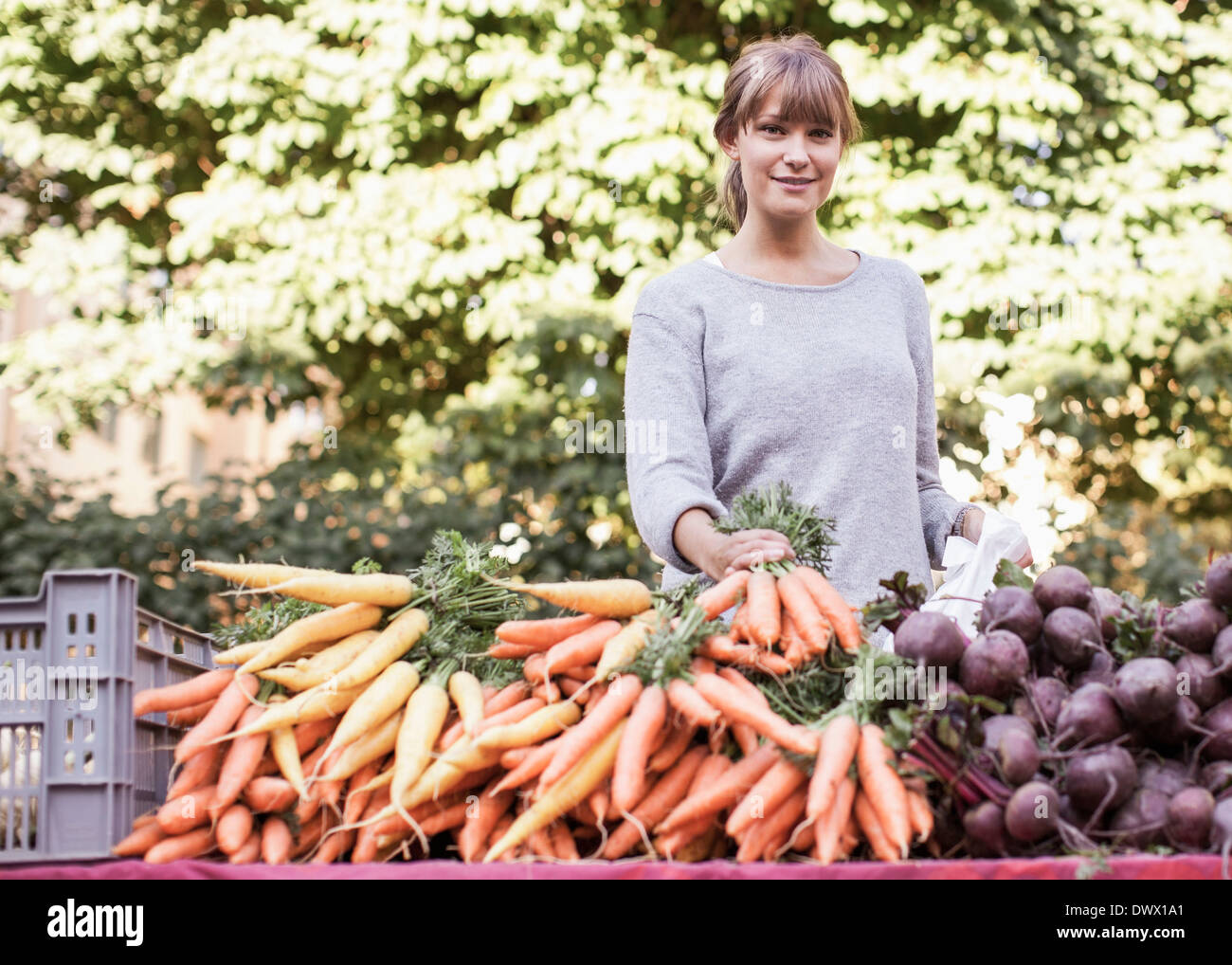 Portrait of smiling female vendor selling vegetables at market stall - Stock Image
