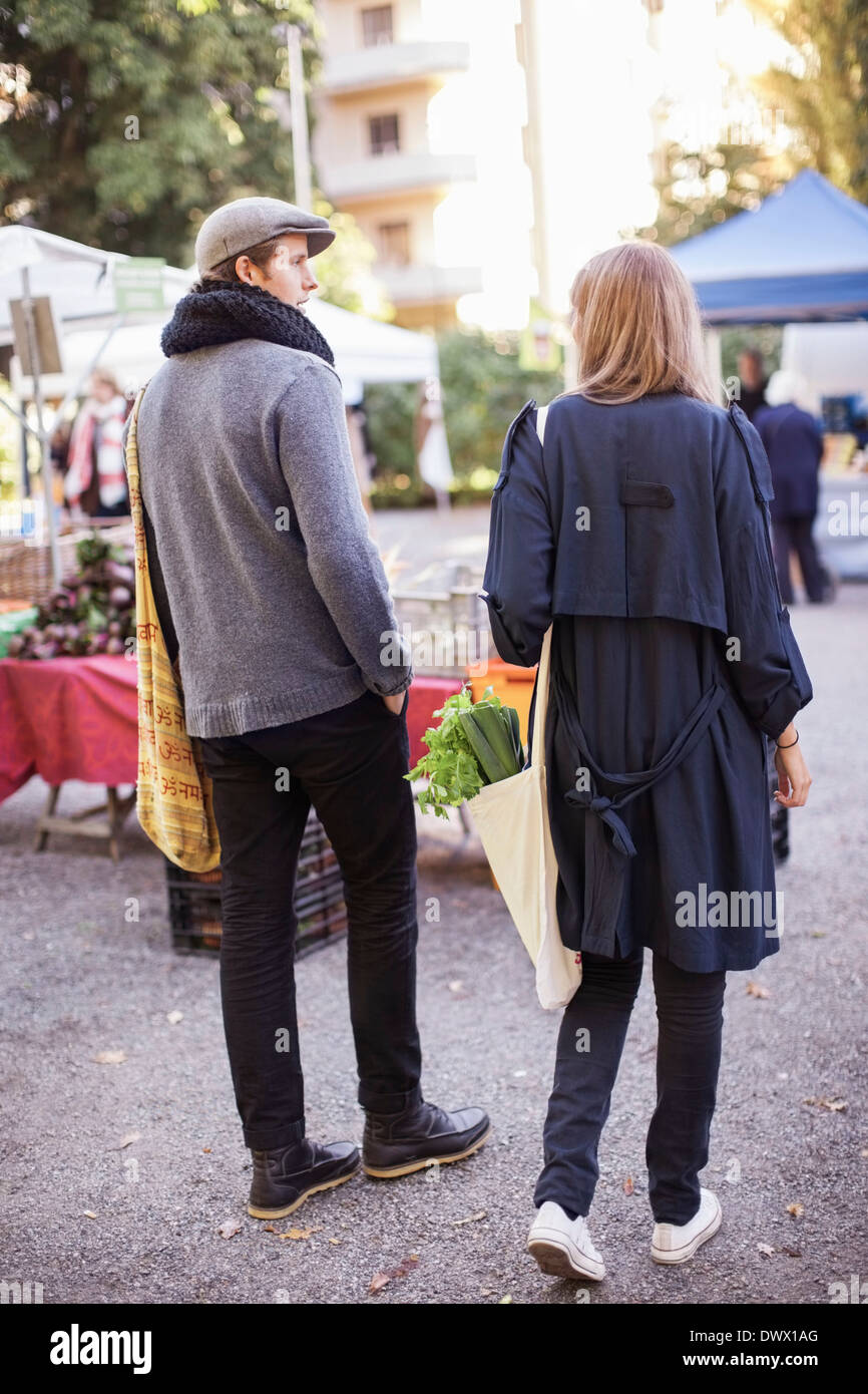 Rear view of young couple with leafy vegetables at market - Stock Image