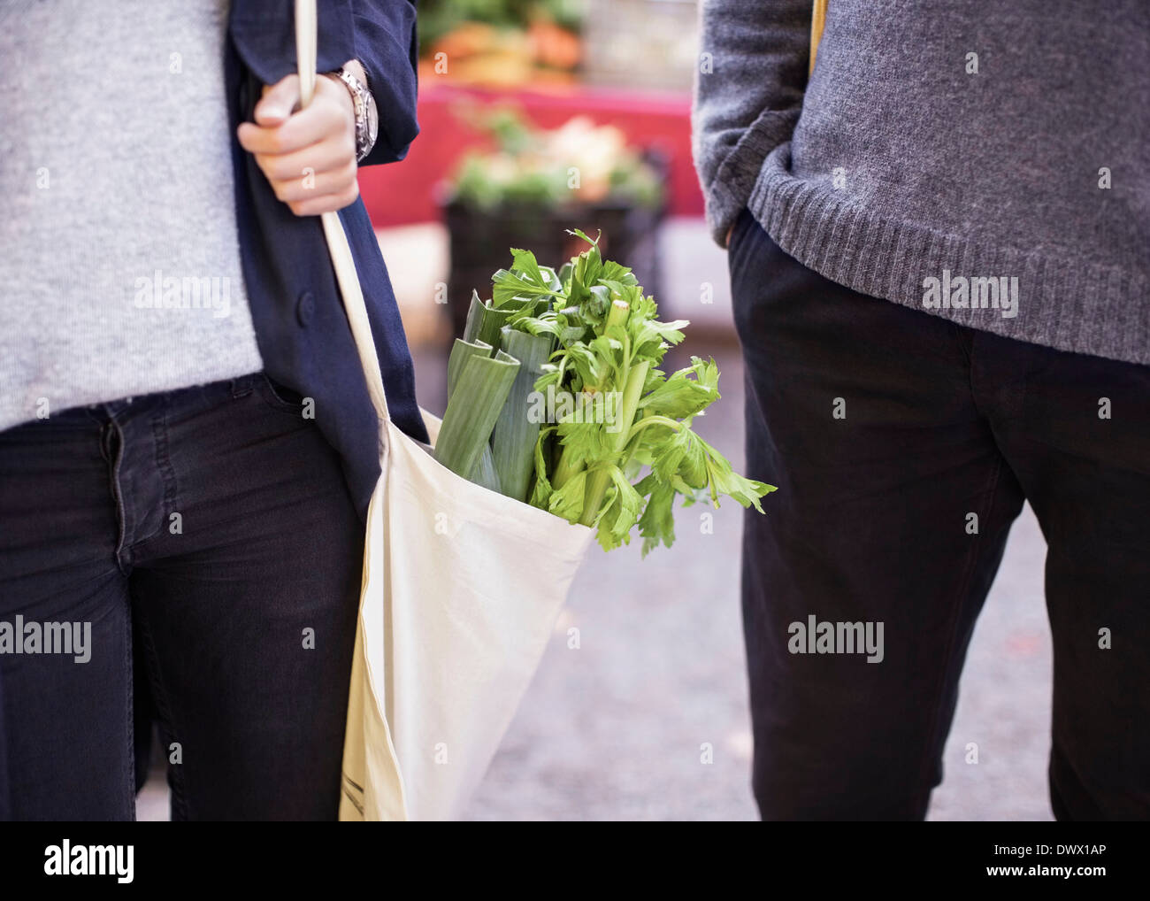 Midsection of couple with leafy vegetables outdoors - Stock Image