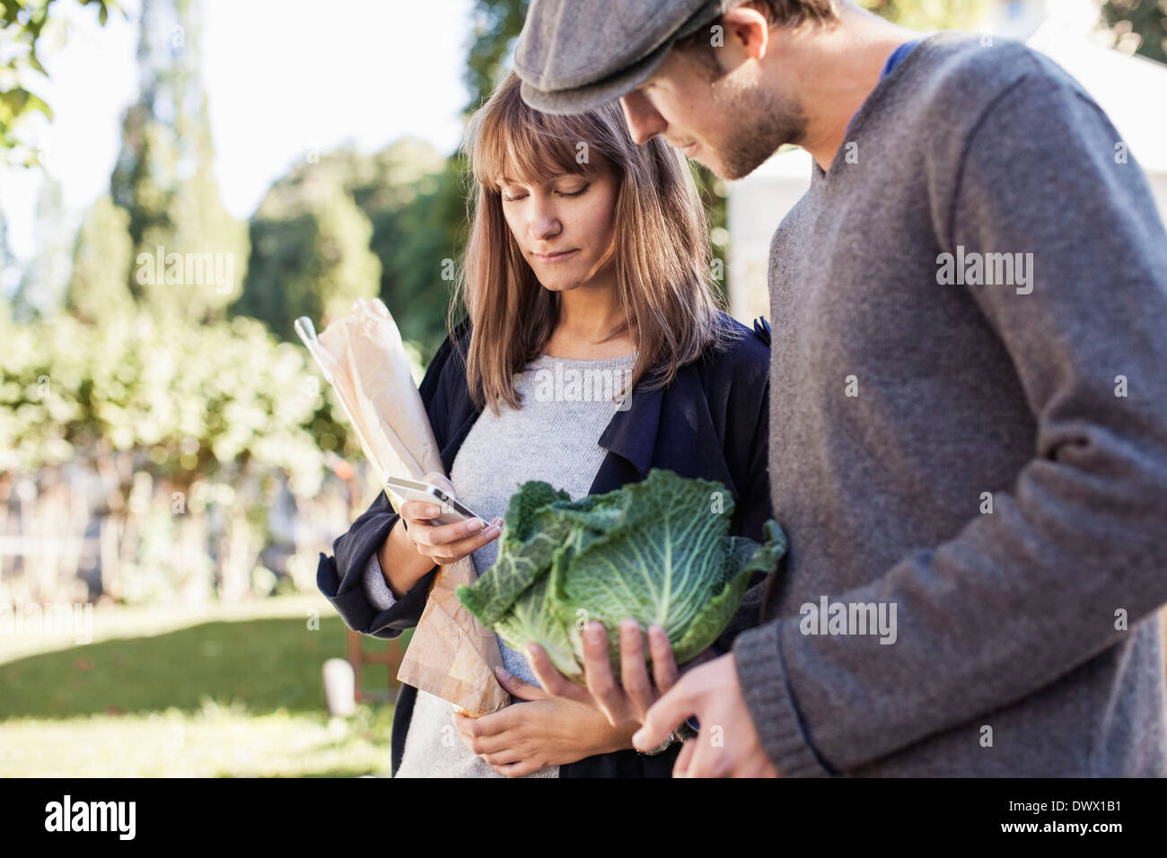 Young couple using mobile phone while buying vegetables in market - Stock Image