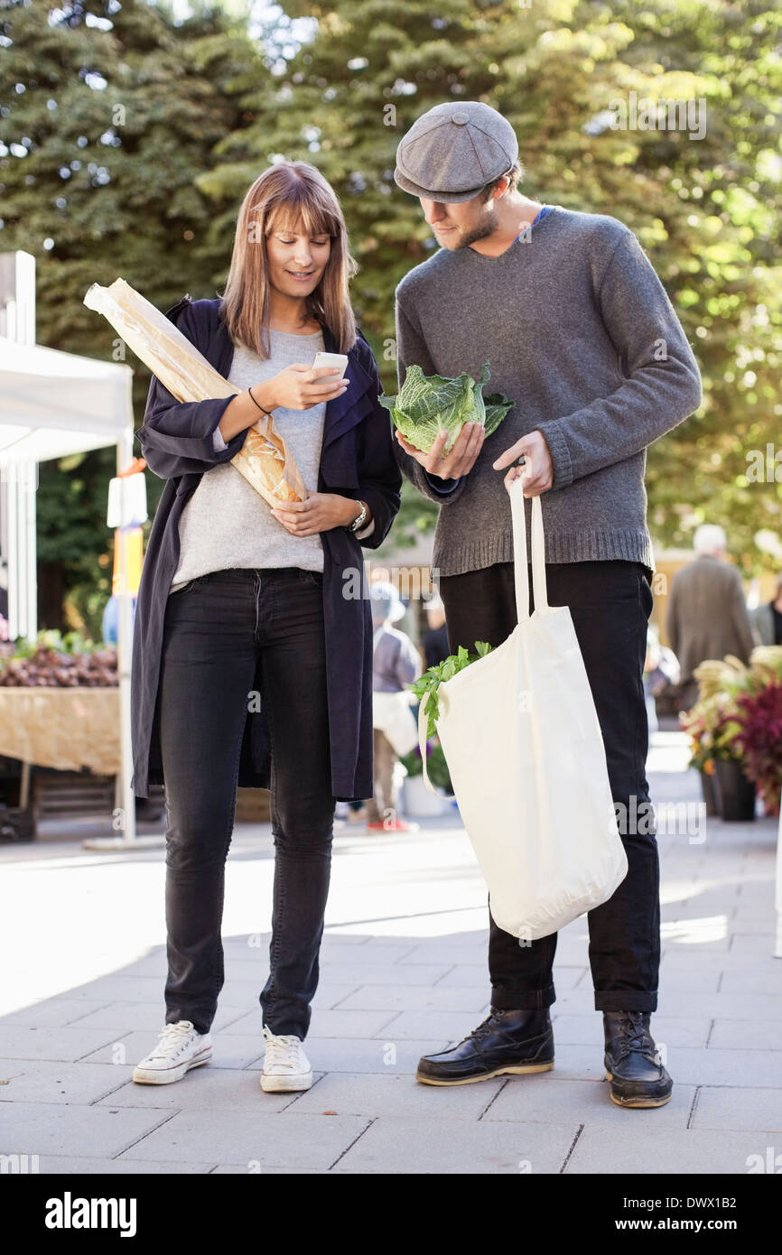 Full length of couple using mobile phone while shopping vegetables in market - Stock Image