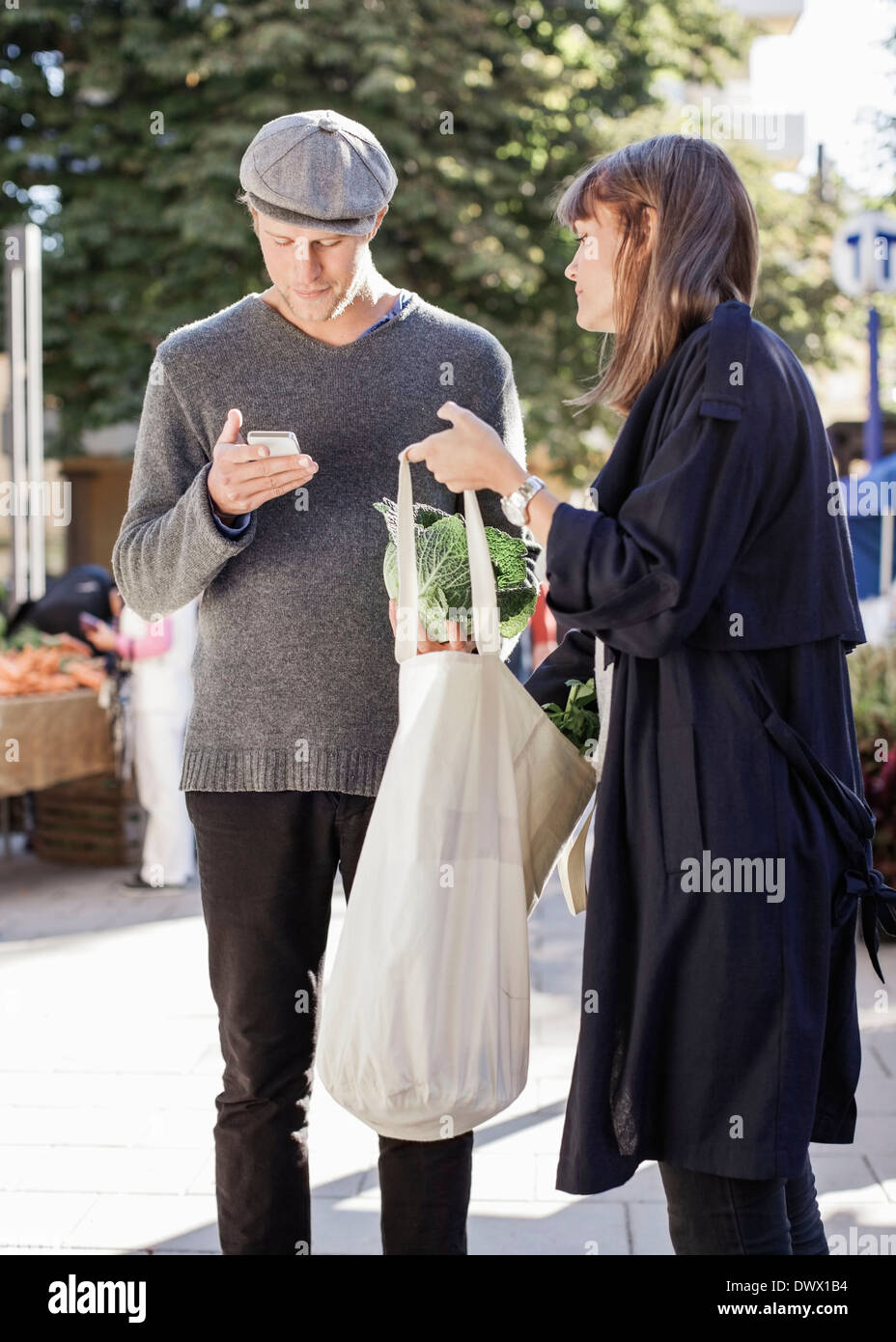 Couple checking list while shopping groceries at market - Stock Image