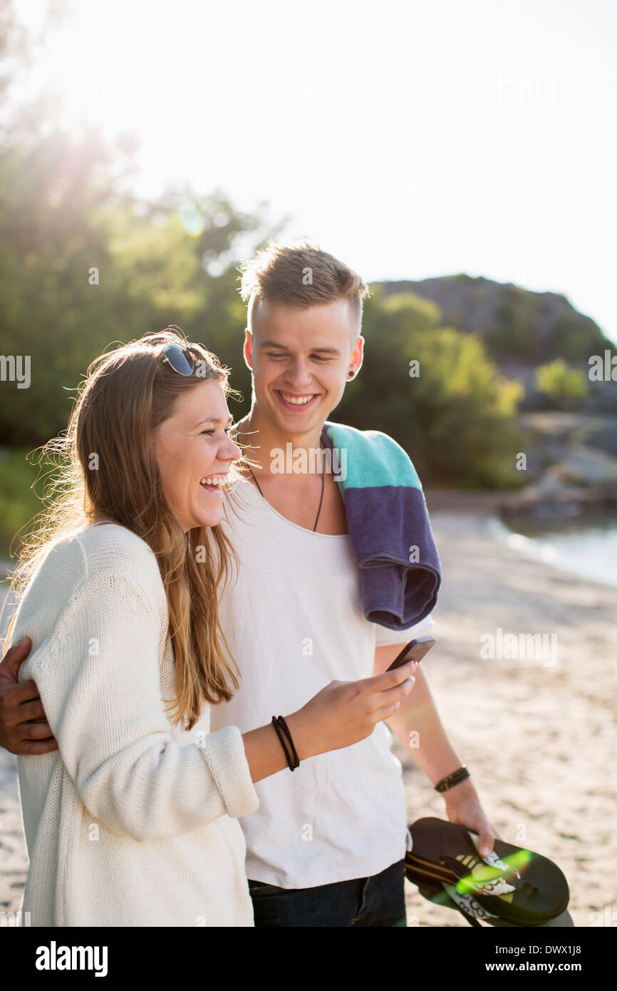 Happy couple spending leisure time on lakeshore - Stock Image