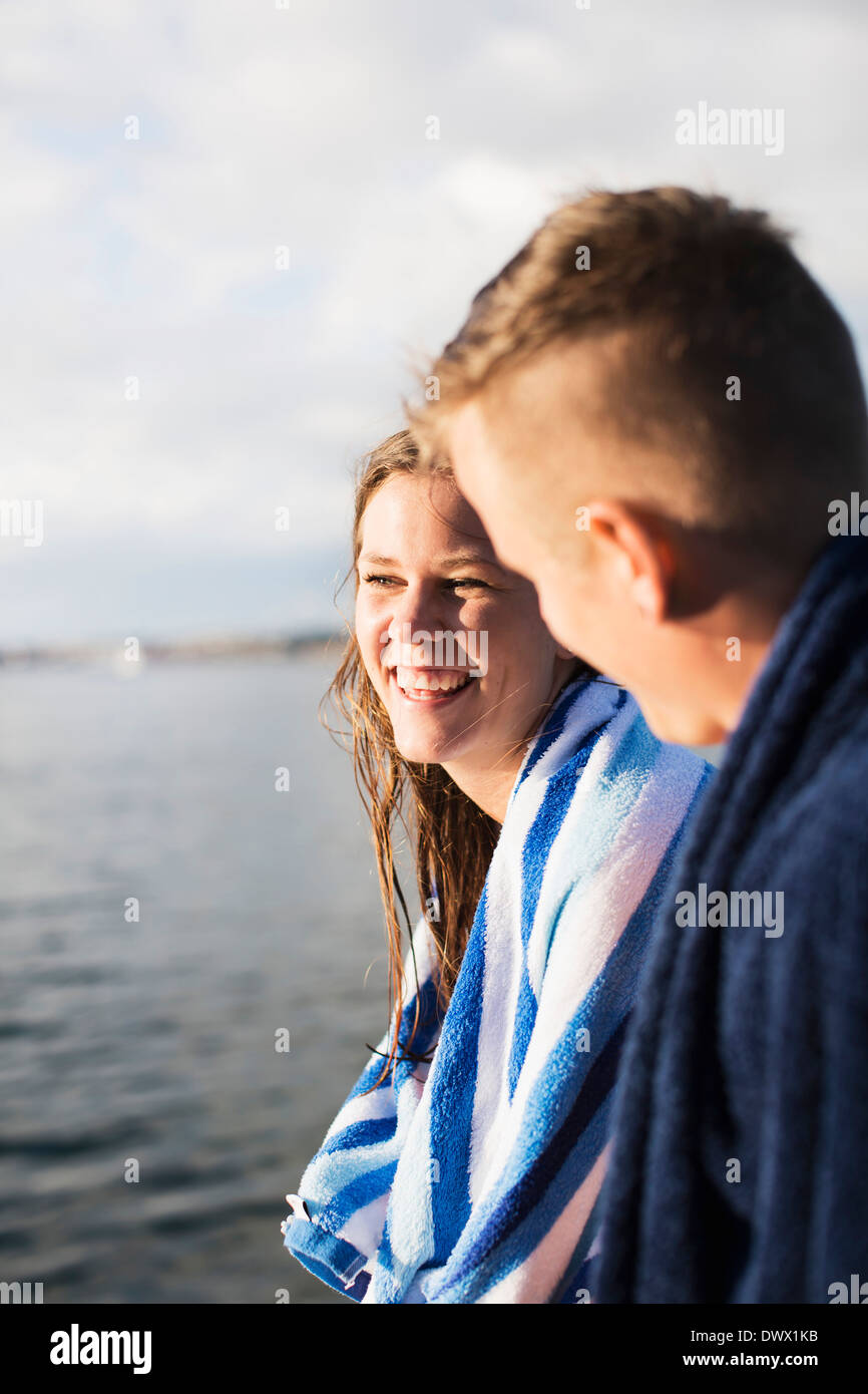 Young couple with towels around neck by lake - Stock Image