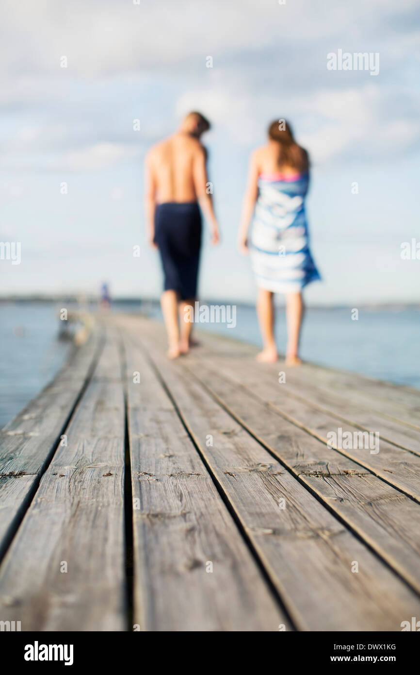 Couple wrapped in towels walking on wooden pier - Stock Image