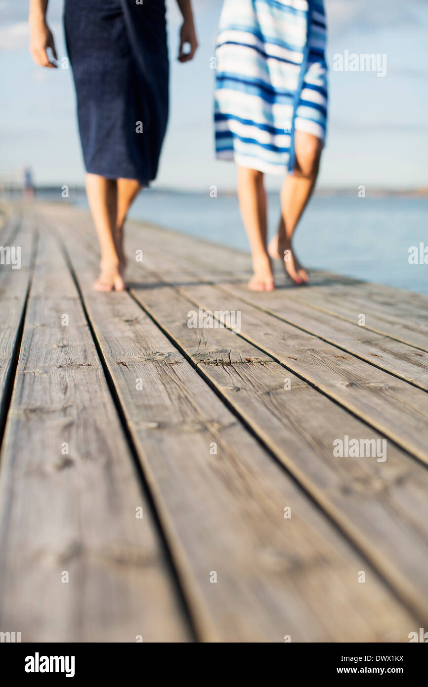Low section of couple wrapped in towels walking on wooden pier Stock Photo