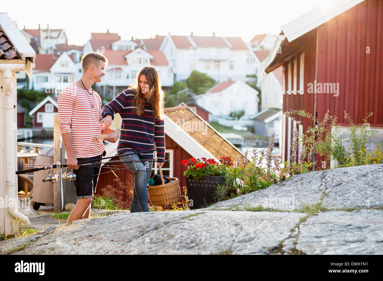 Young couple with basket and fishing rods walking outdoors - Stock Image