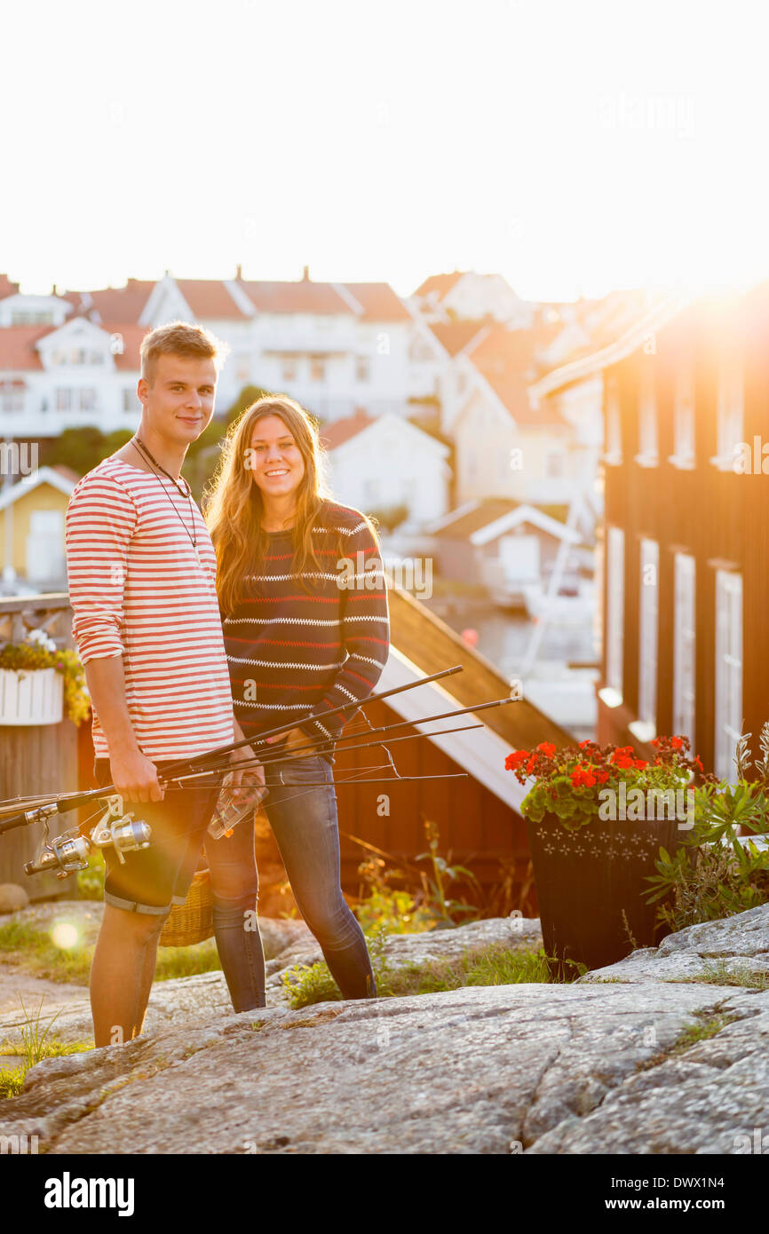 Portrait of smiling couple with fishing rods standing on rock - Stock Image