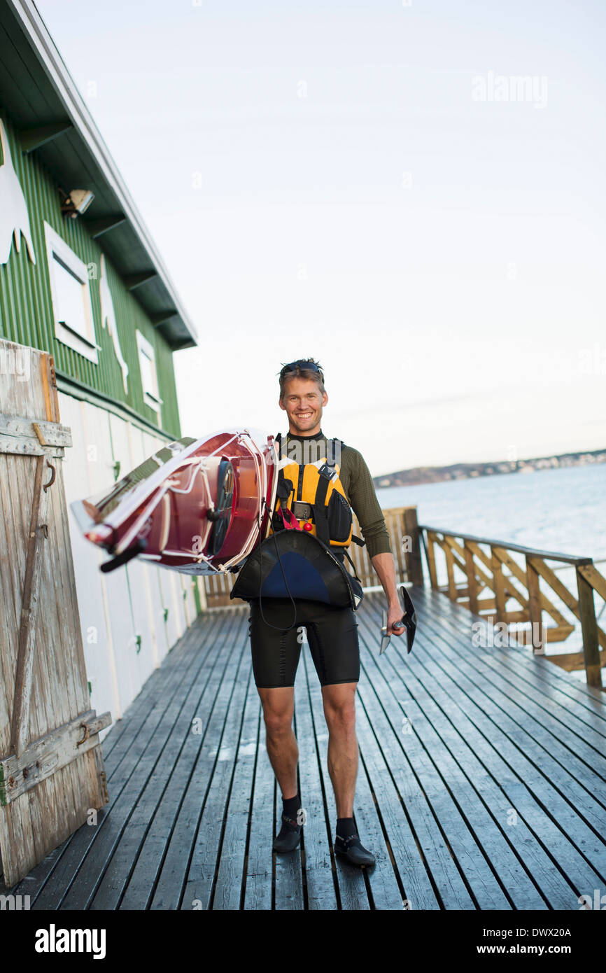 Full length portrait of happy man carrying kayak on shoulder at boathouse - Stock Image