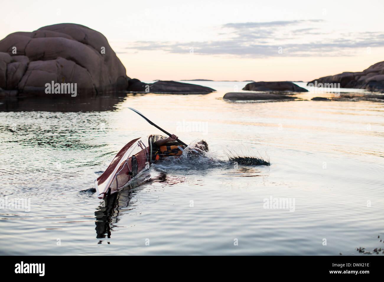 Man falling into water while kayaking - Stock Image