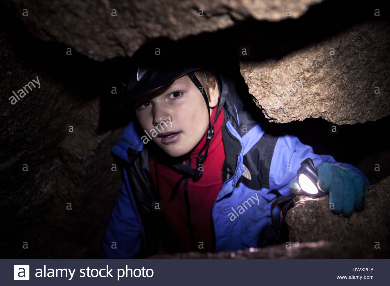 Portrait of boy with flashlight in cave - Stock Image