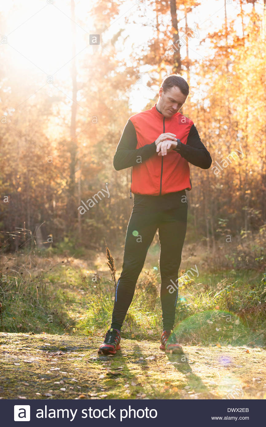 Full length of runner checking time in forest - Stock Image