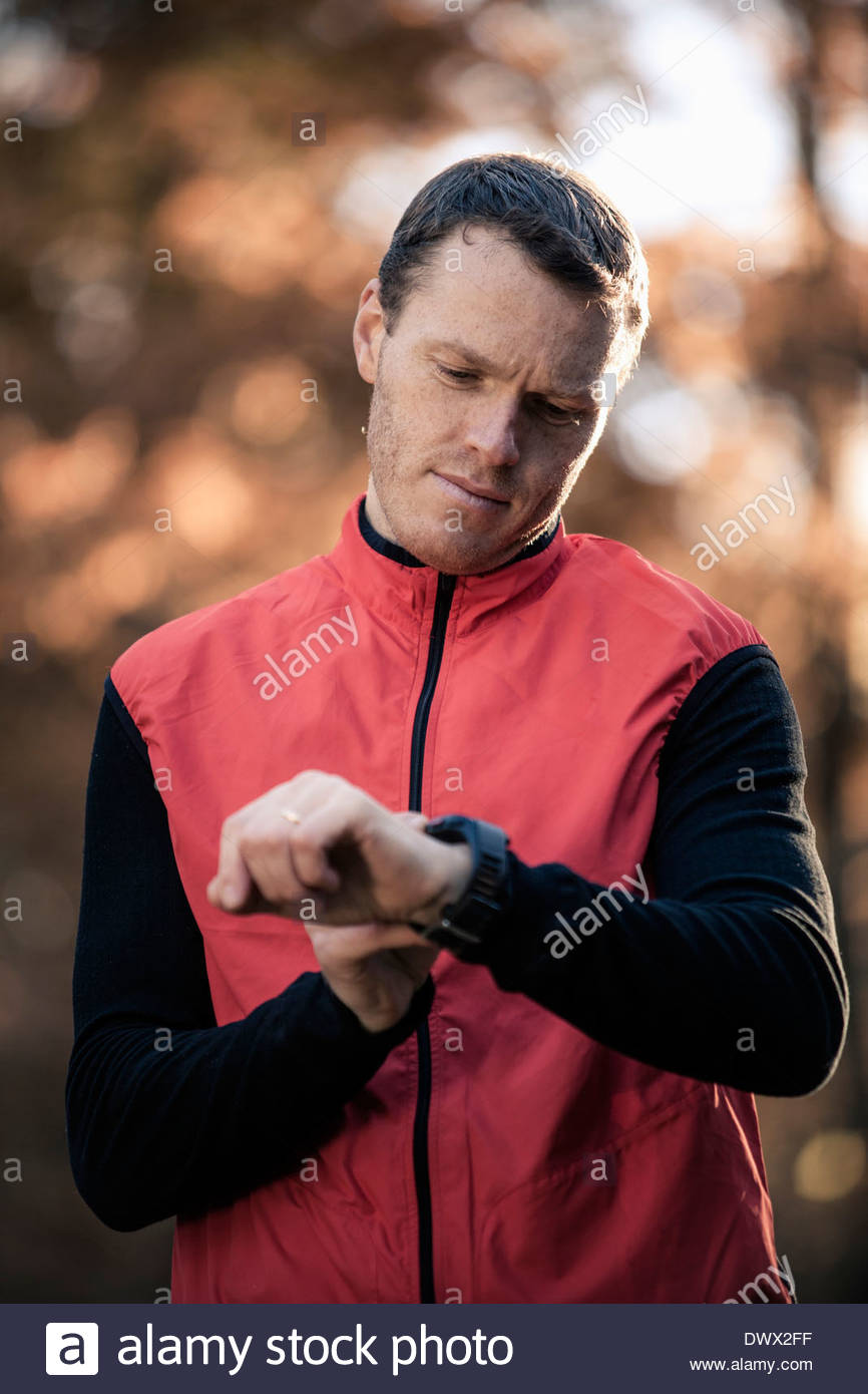 Male runner checking time in forest - Stock Image