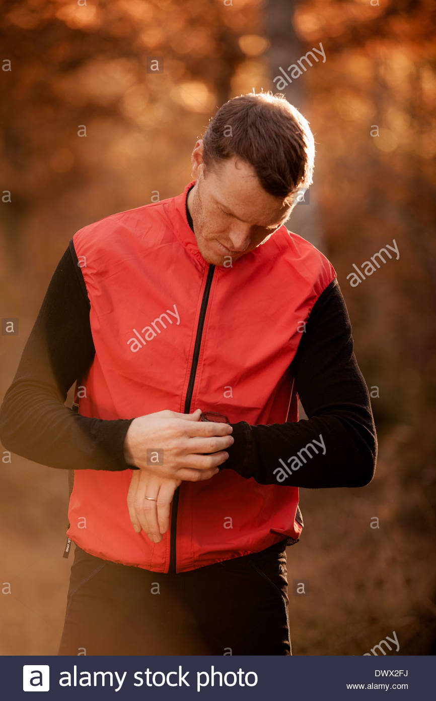 Man in sportswear checking time in forest - Stock Image