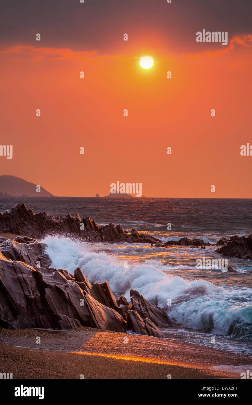 Sunrise view of waves crashing onto the rocks at Slapton Sands, Devon, UK - Stock Image